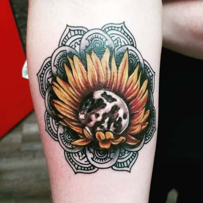 large black and color tattoo on lower leg of a sunflower with a moon in its center and a mandala around it