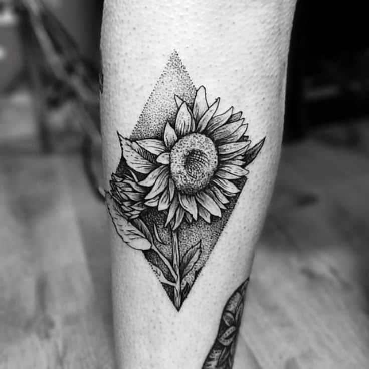 medium-sized black and grey dotwork tattoo on man's lower leg of a dark realistic sunflower and leaves inside a triangle