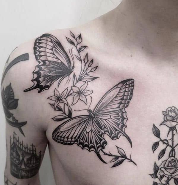large black and grey tattoo on man's chest and shoulder of two realistic butterflies with a flower vine between