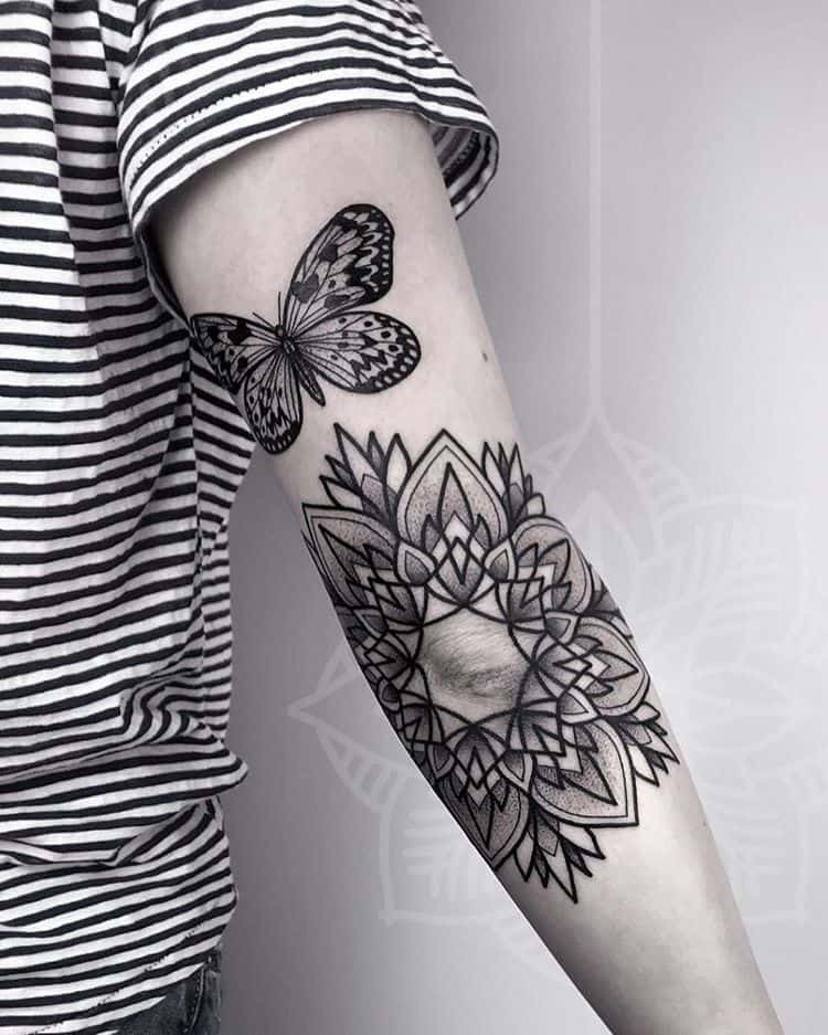 medium-sized black and grey tattoo on back of arm of a realistic butterfly with large mandala below