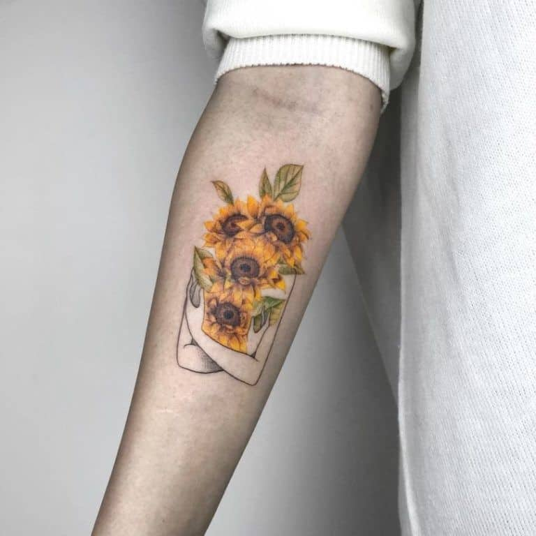 medium-sized color tattoo on man's forearm of the upper half of a woman holding realistic sunflowers over her body and face