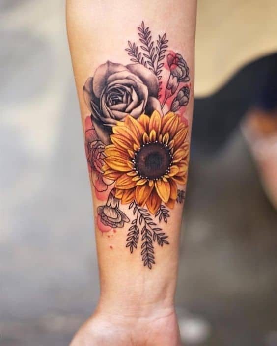 large color and black and grey watercolor tattoo on woman's forearm of a realistic sunflower and roses