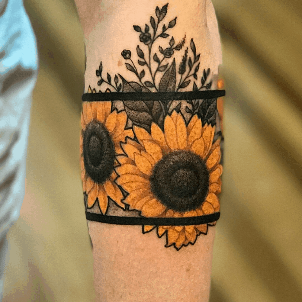 large black and color tattoo on forearm of two realistic sunflowers with two bold parallel lines wrapping around arm