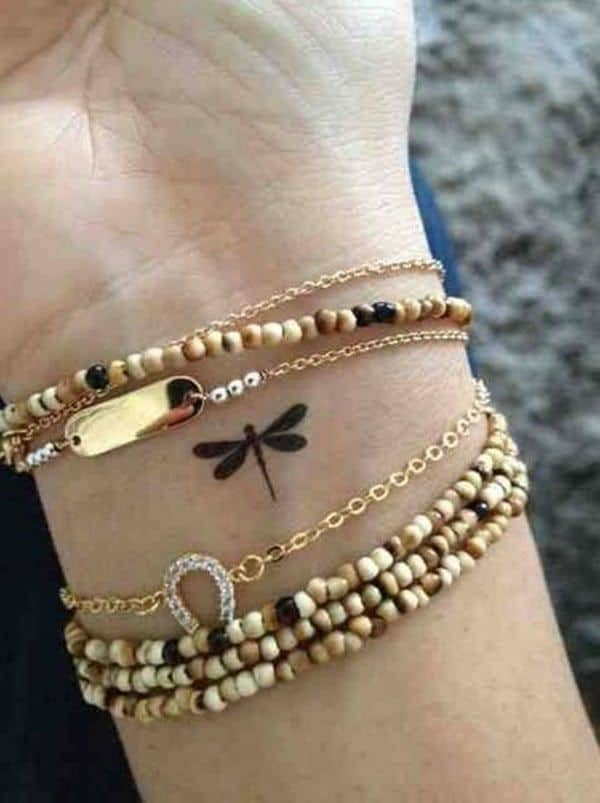 A miniature dragonfly sitting peacefully in the beaded bracelets on the wrist