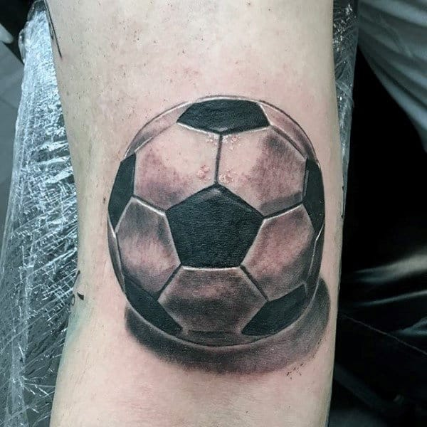 Soccer ball tattoo design featuring 3D shading on man's arm