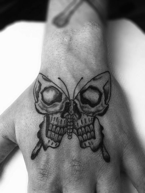 large black and grey tattoo on man's hand of a surrealistic butterfly with skull face in its wings