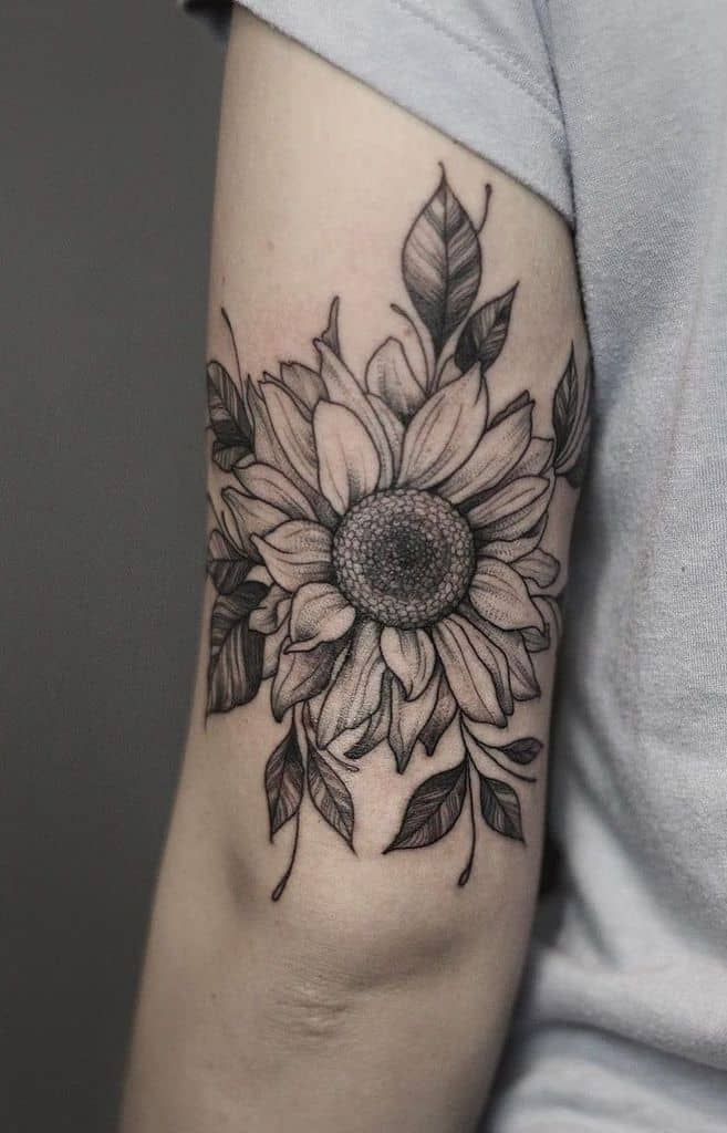large black and grey tattoo on back of upper arm of realistic sunflower with leaves around it