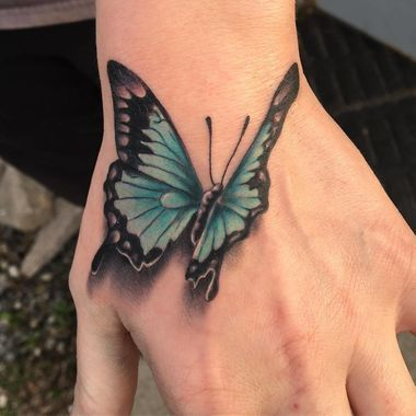 medium-sized color tattoo on man's hand of a realistic blue butterfly with shadow