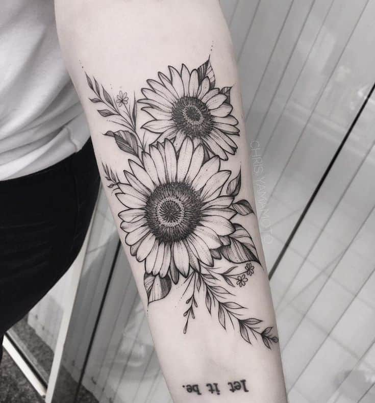 large black and grey tattoo on woman's forearm of two realistic sunflowers with leaves and vines behind it