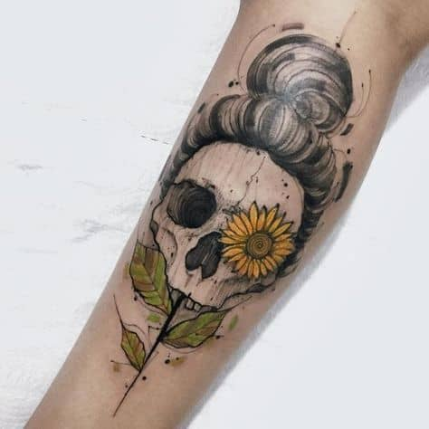 large black and color tattoo on lower leg of female skull with hair in a bun and sunflower in eye with stem growing in mouth