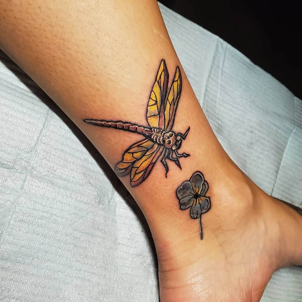 The lily-livered dragonfly flying to the amber flower showing the attractiveness