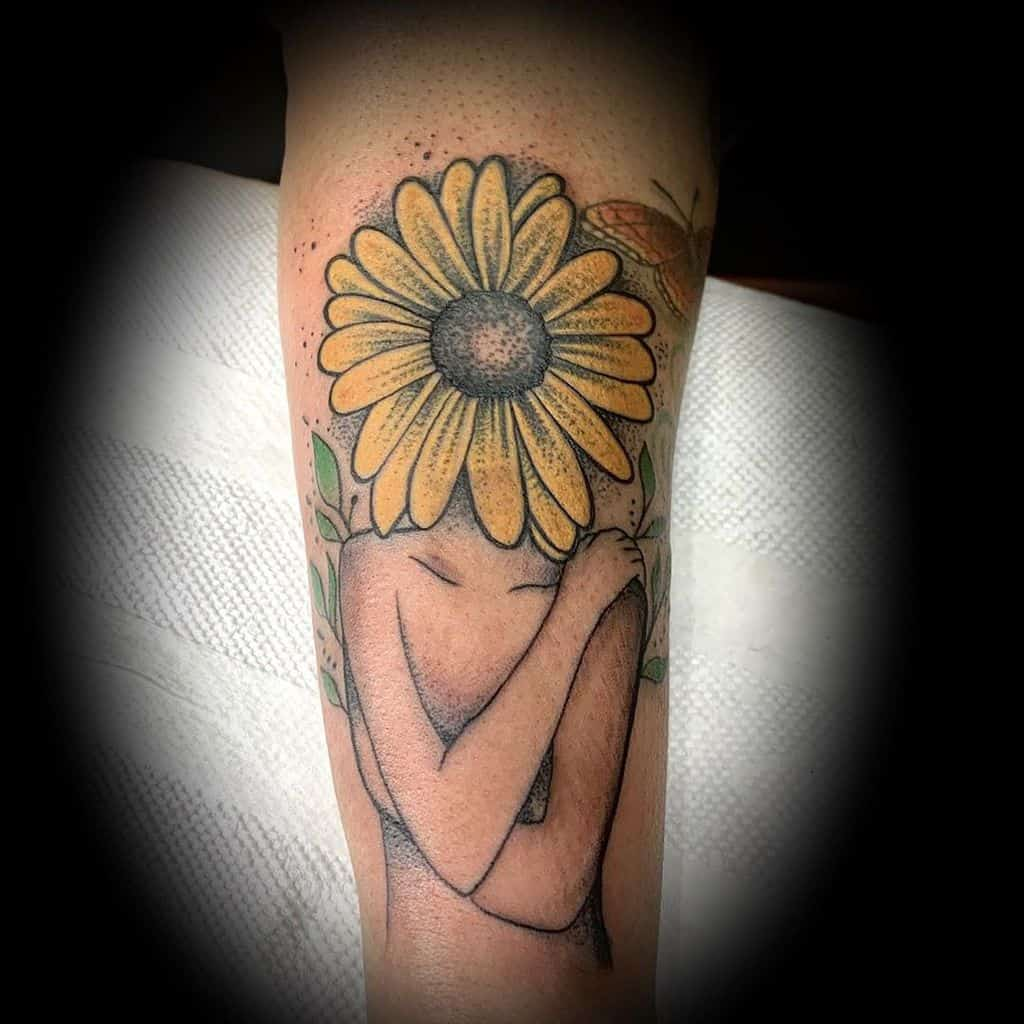 large color tattoo on forearm of traditional naked woman with sunflower as head and leaves and butterfly around it