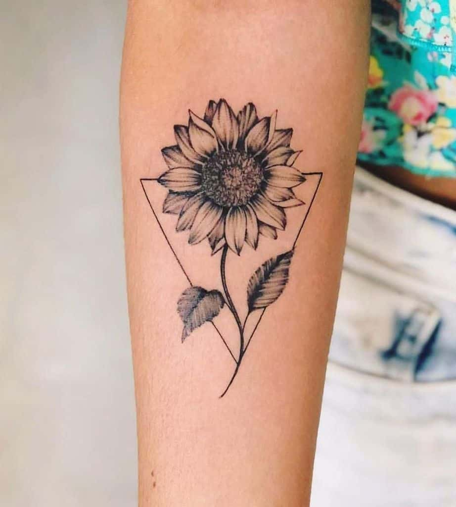 medium-sized black and grey tattoo on forearm of realistic sunflower with stem and leaves inside geometric triangle