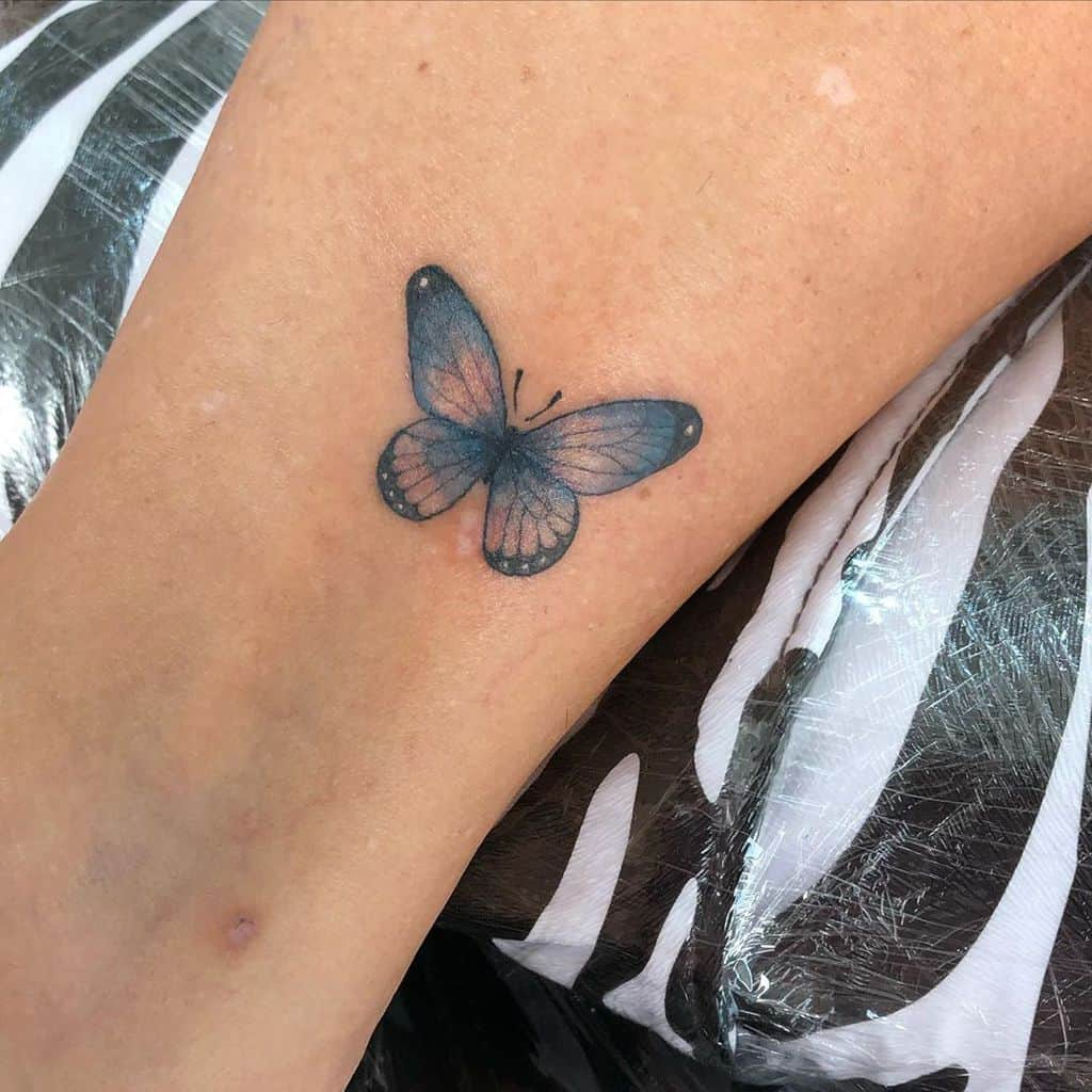 small color tattoo on woman's lower leg of a delicate realistic blue butterfly