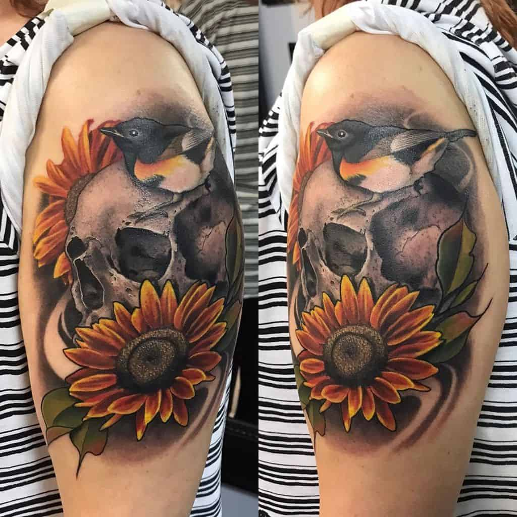 large traditional color tattoo on woman's upper arm of two sunflowers, a skull, and a bird