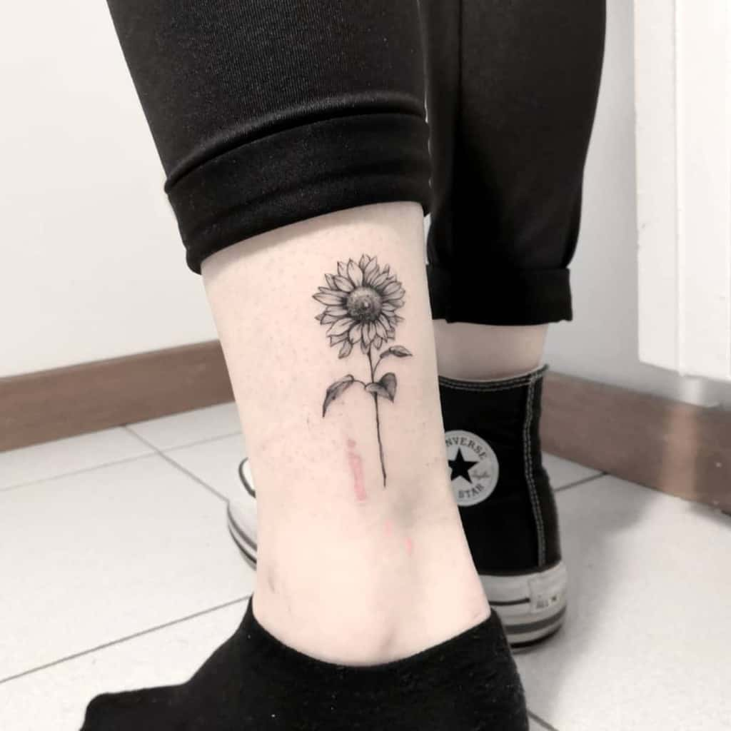 black and gray realistic tattoo on woman's ankle of realistic sunflower with stem