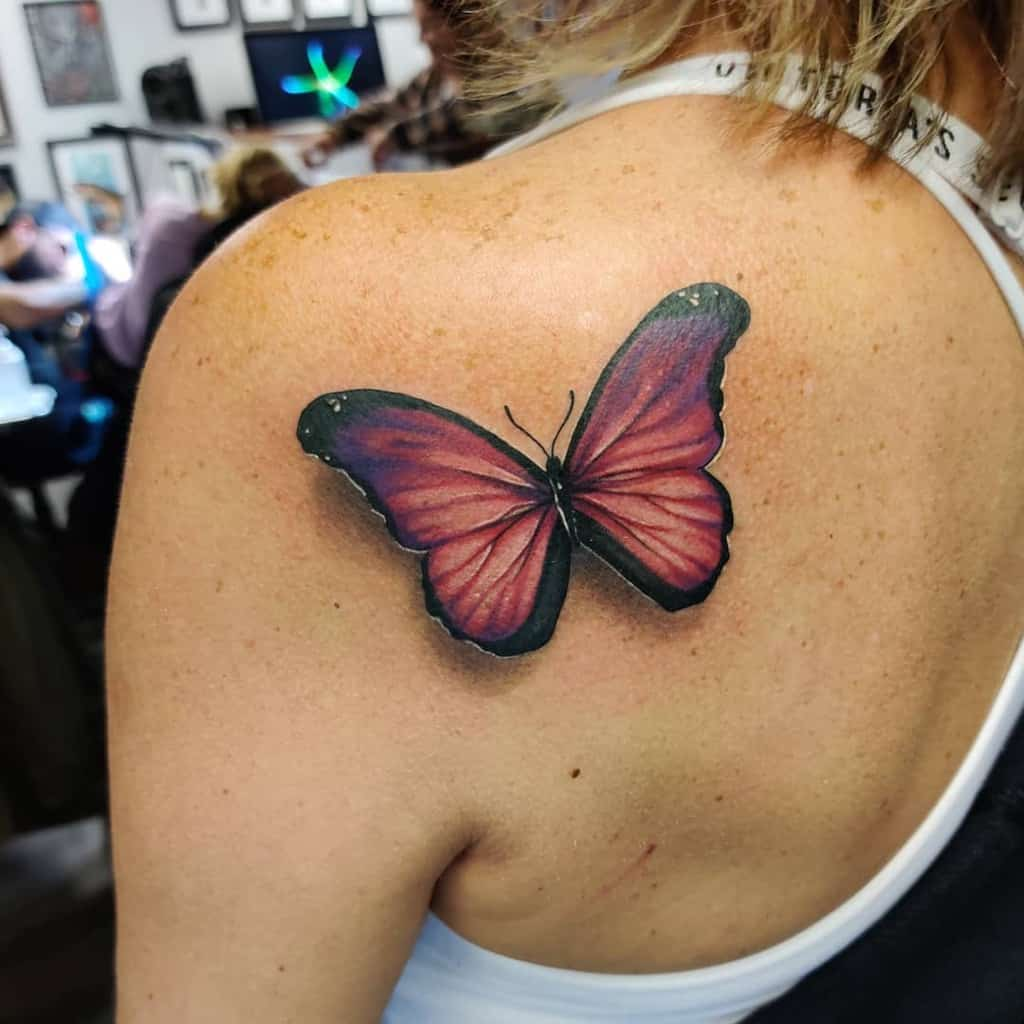large color tattoo on woman's shoulder of realistic pink butterfly with shadow
