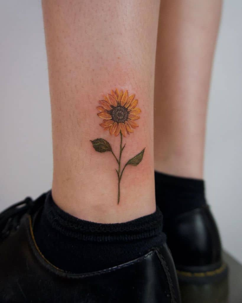 realistic colored tattoo on a woman's ankle of a dainty sunflower