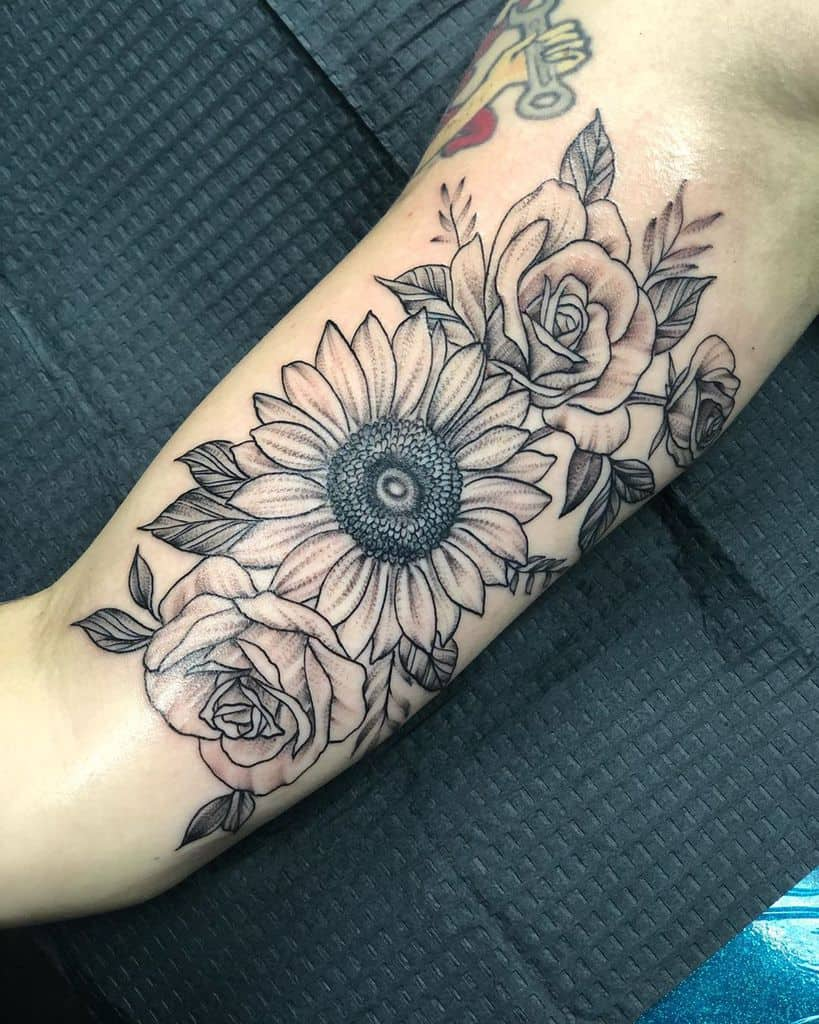 large black and grey tattoo on inner upper arm of realistic sunflower with two roses and leaves around them