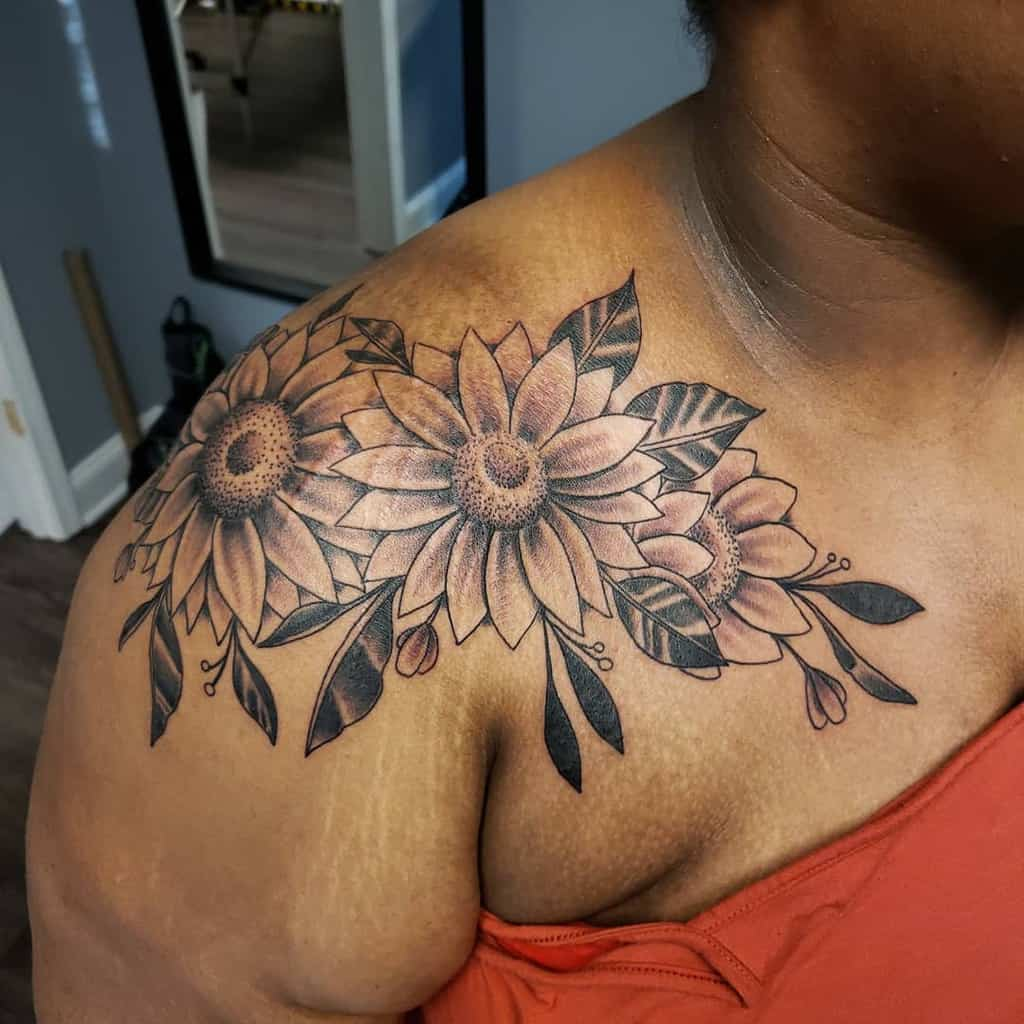 large black and grey tattoo on woman's should and chest of traditional sunflowers