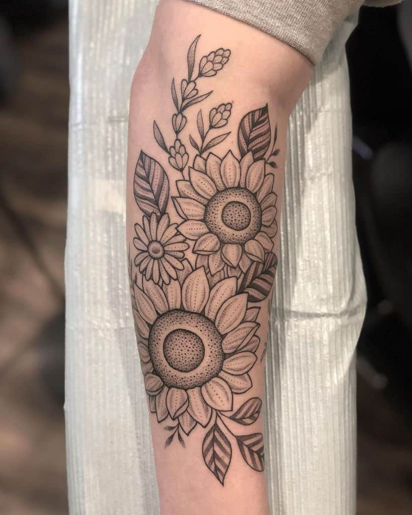 large black and grey traditional tattoo on man's forearm of a bouquet of sunflowers and a daisy with leaves behind them
