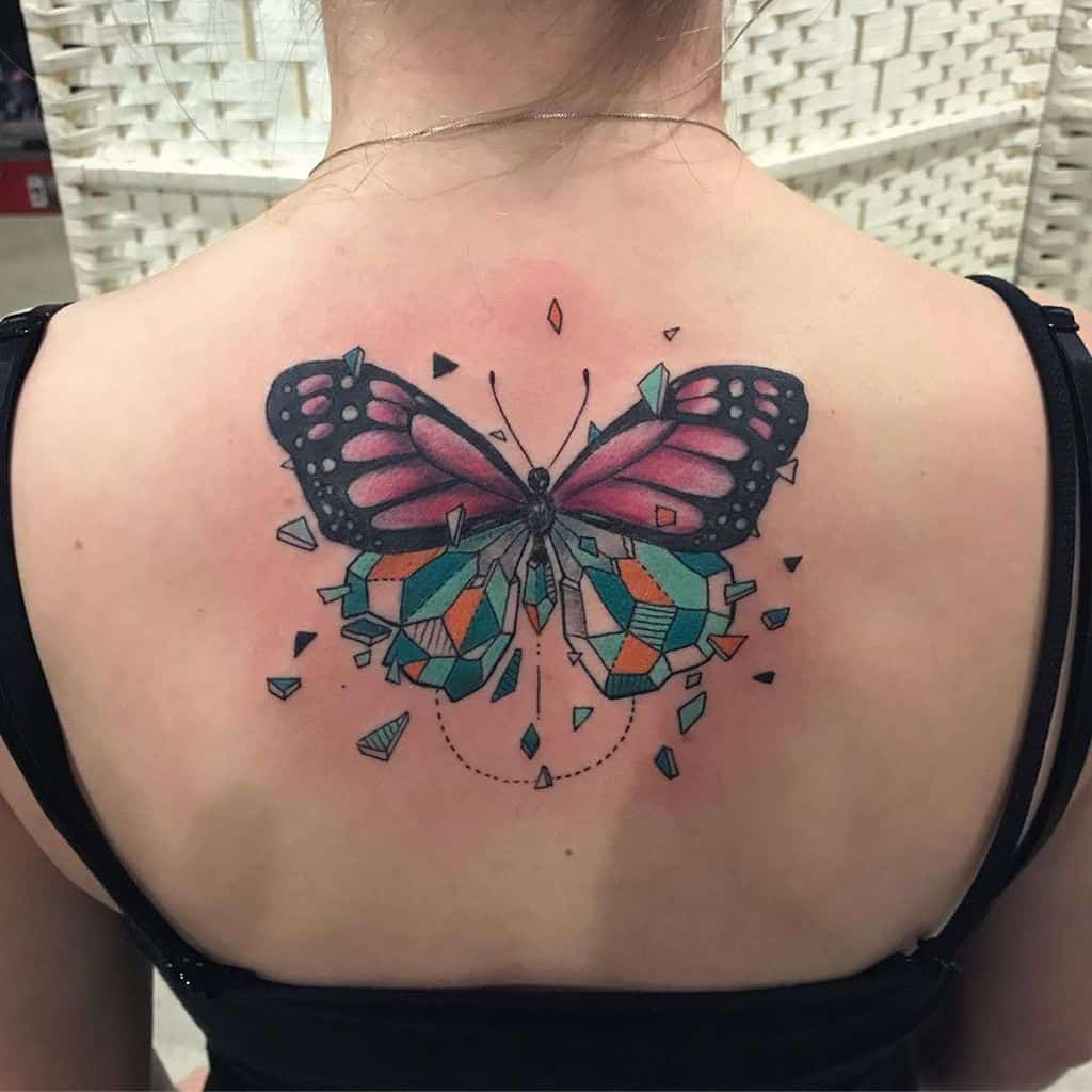 large color geometric tattoo on a woman's upper back of surrealistic butterfly with bottom half made of shattering crystals
