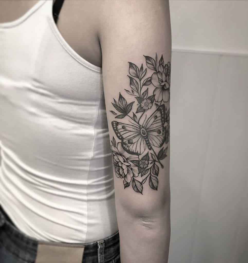 large black and grey tattoo on woman's upper arm of butterfly with flowers and leaves around it
