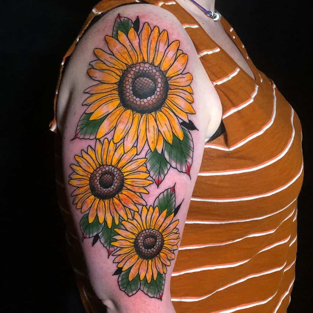 large color traditional tattoo on woman's upper arm of three sunflowers