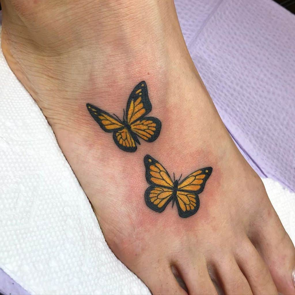 small color tattoo on woman's foot of two realistic yellow butterflies