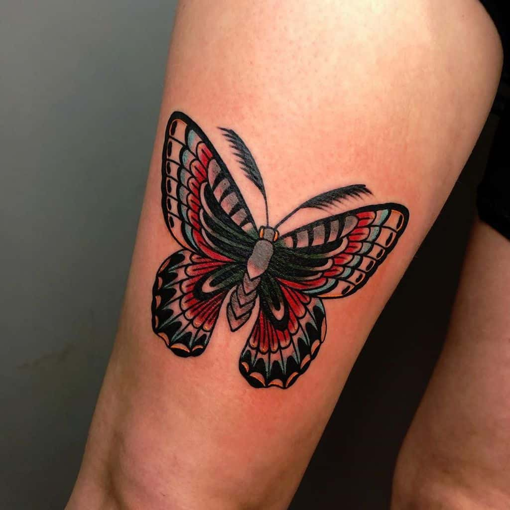 large color tattoo on thigh of a traditional blue and red butterfly