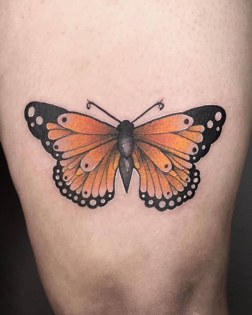 medium-sized color tattoo on woman's thigh of orange realistic butterfly
