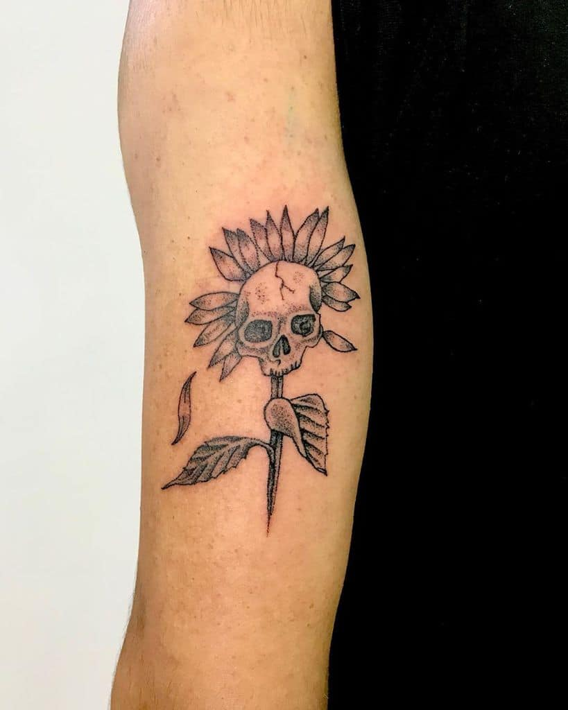 medium-sized black and grey tattoo on back of man's upper arm of a sunflower with a skull in its center and a stem