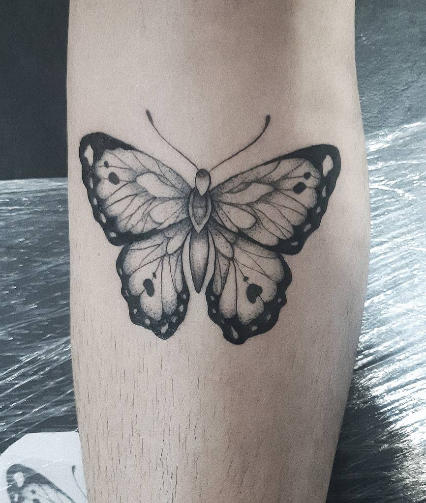 medium-sized black and grey tattoo on lower leg of a realistic delicate butterfly