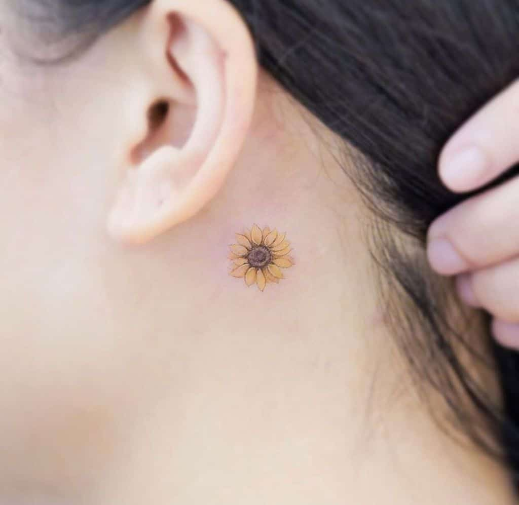 tiny colored realistic sunflower tattooo behind woman's ear