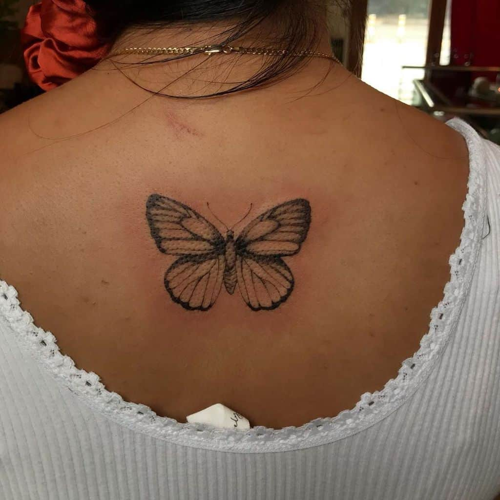 medium-sized black and grey tattoo on woman's upper backof realistic butterfly