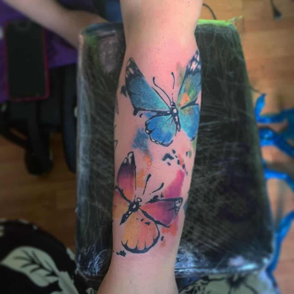 large color watercolor tattoo on woman's forearm of two surrealistic butterflies