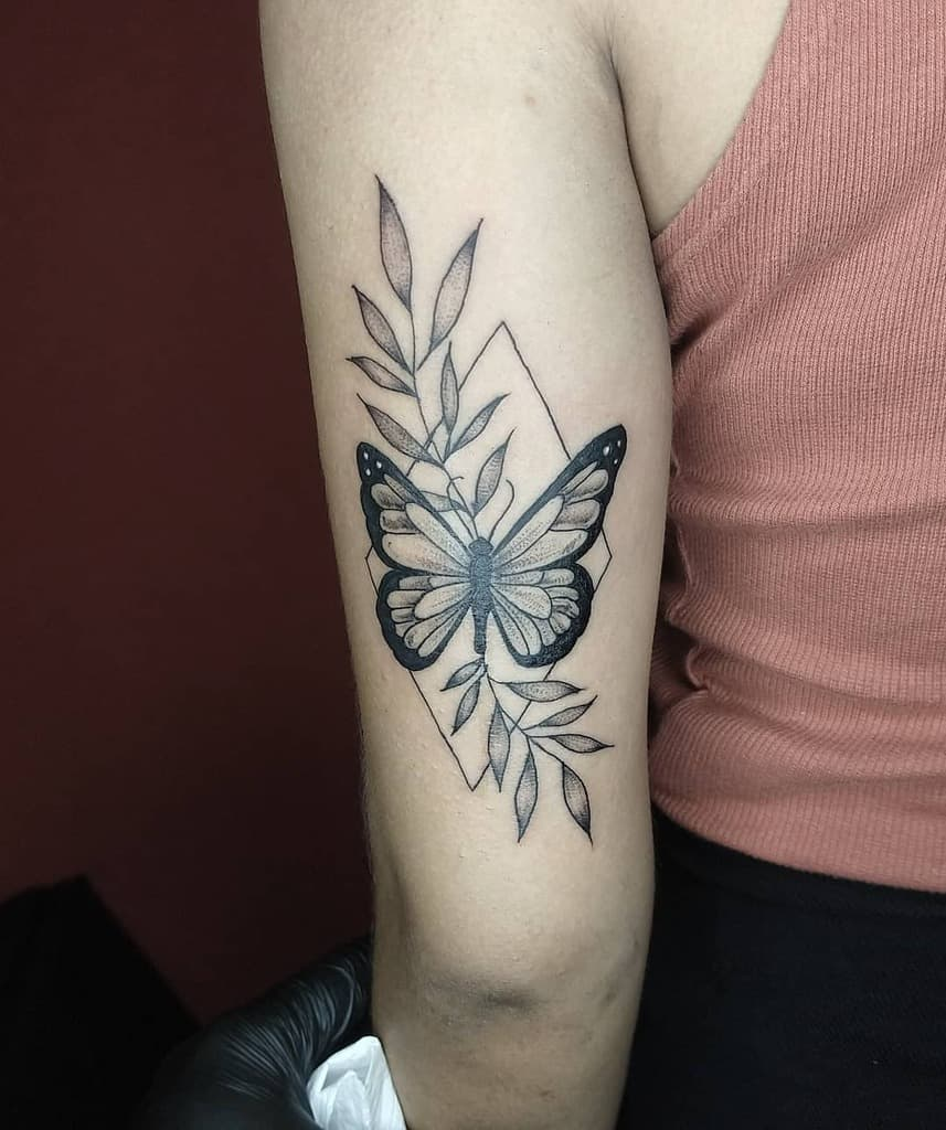 medium-sized geometric black and grey tattoo on woman's upper arm of realistic butterfly in rhombus diamond with leaves