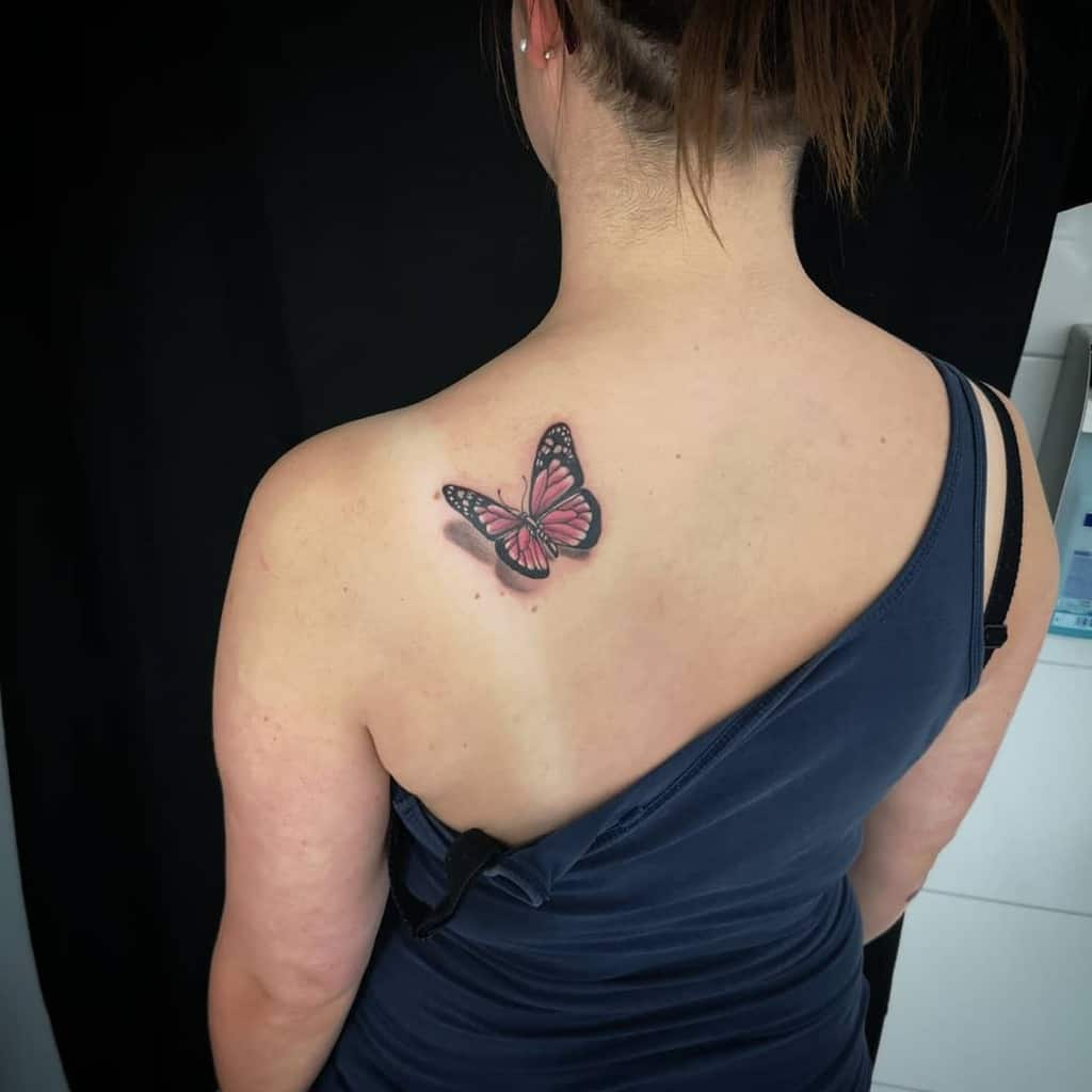 medium-sized color tattoo on woman's shoulder of pink flying butterfly with shadow