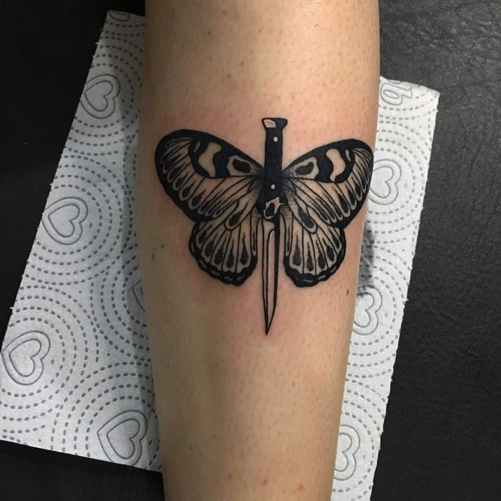 medium-sized black and grey tattoo on lower leg of a butterfly with dagger or knife in the middle