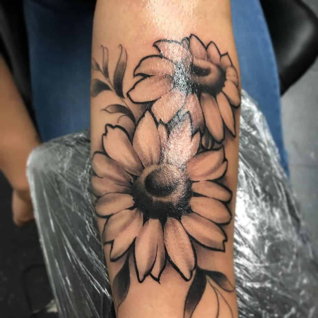 large black and grey tattoo on forearm of two traditional sunflowers with leaves around them