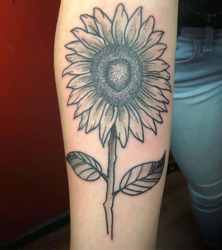 large black and grey realistic sunflower on woman's forearm
