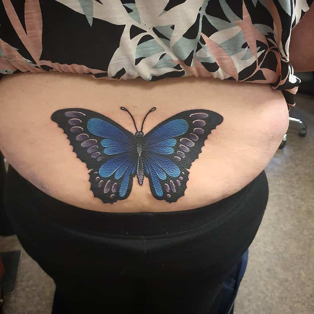large color tattoo on woman's lower back of blue monarch butterfly