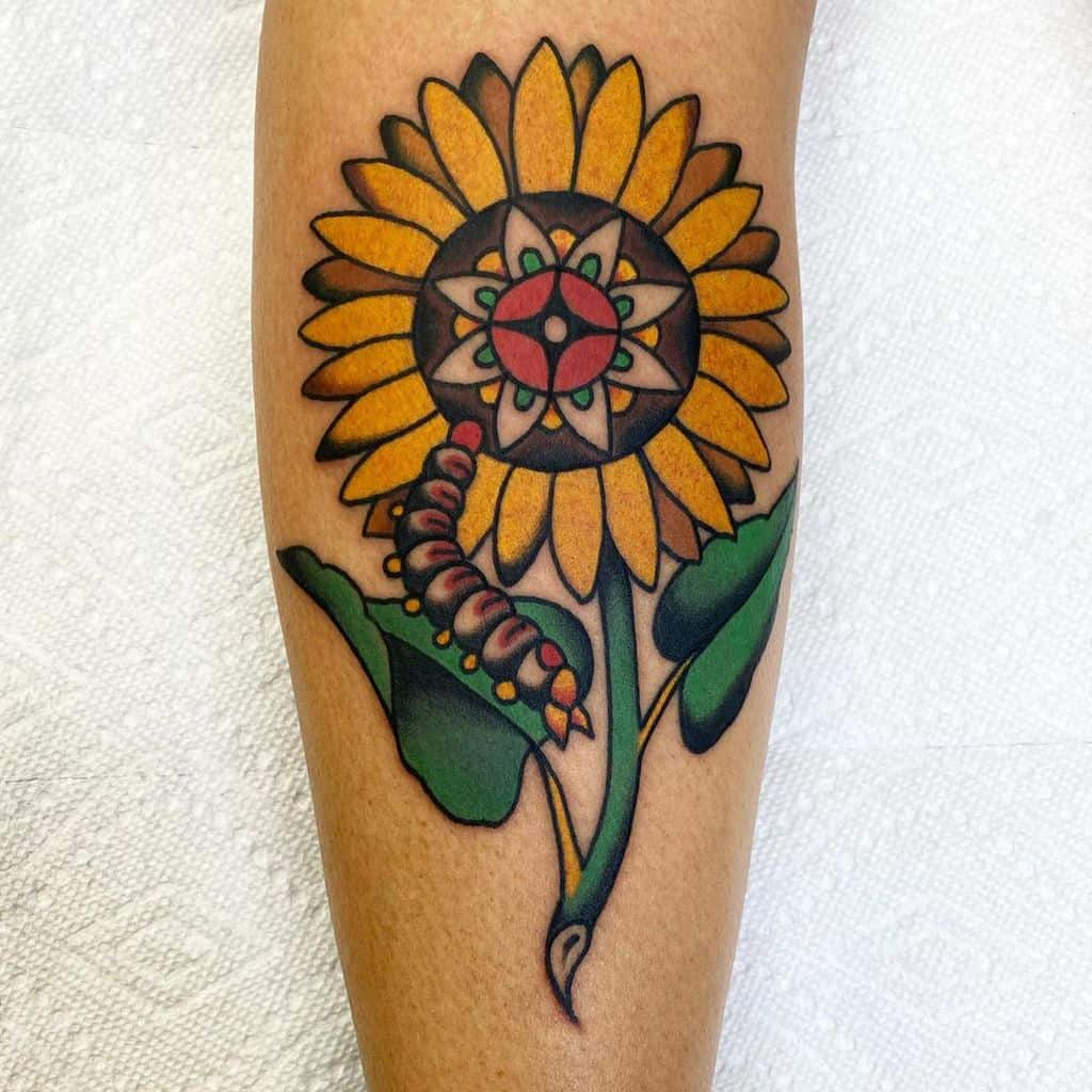 large tattoo on lower leg of colored traditional sunflower and caterpillar
