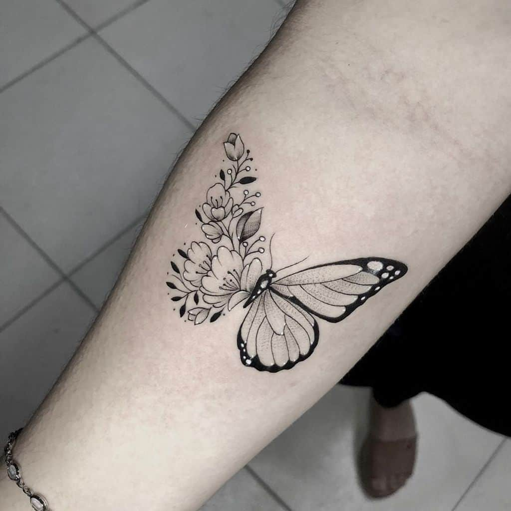medium-sized black and grey tattoo on woman's forearm of butterfly with one floral wing