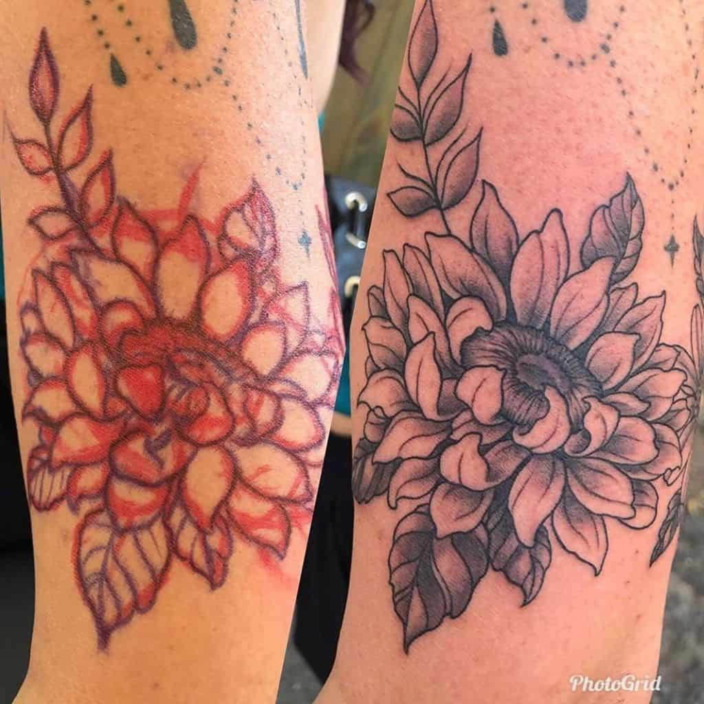 medium-sized black and grey tattoo on lower leg of realistic sunflower with leaves around it