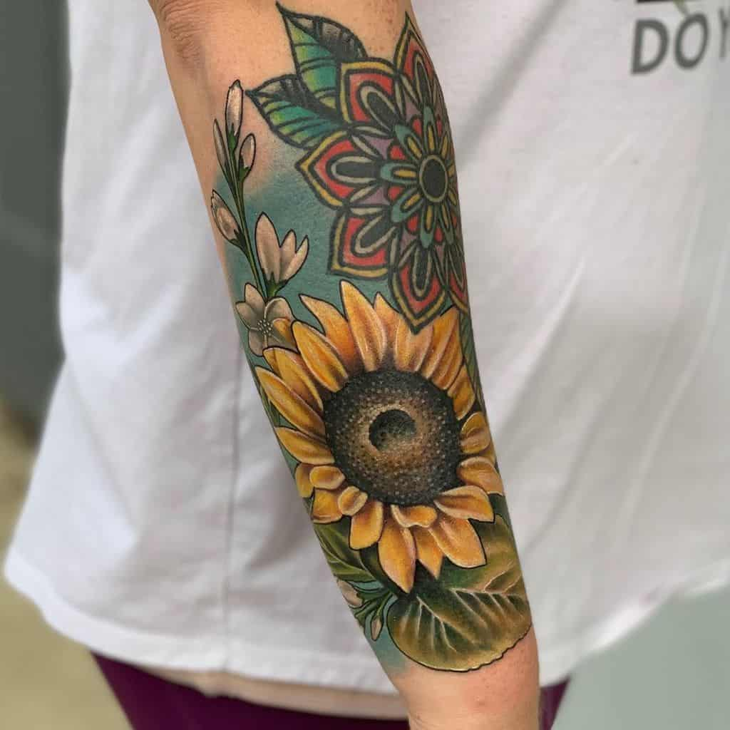 large color half-sleeve tattoo on forearm of realistic sunflower with leaves and water behind and a mandala next to it