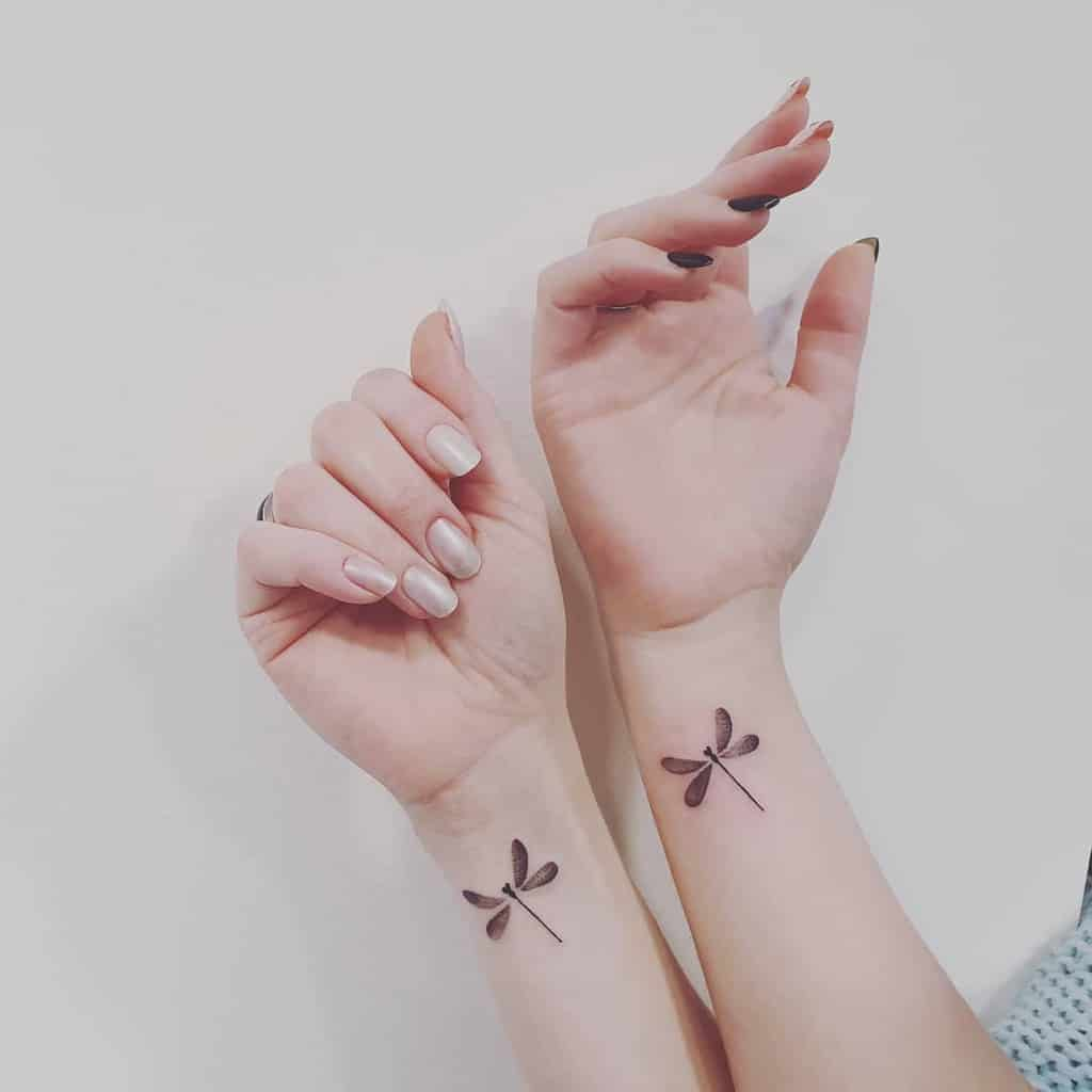 The perfectly drawn dragonfly on the wrists of crafted hands and nude nails