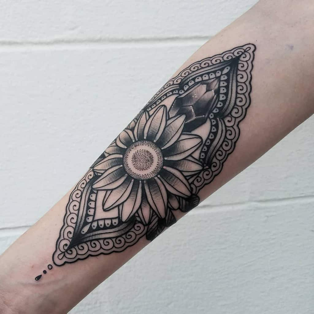 large black and grey traditional tattoo on forearm of symmetrical sunflower with ornamental henna behind it