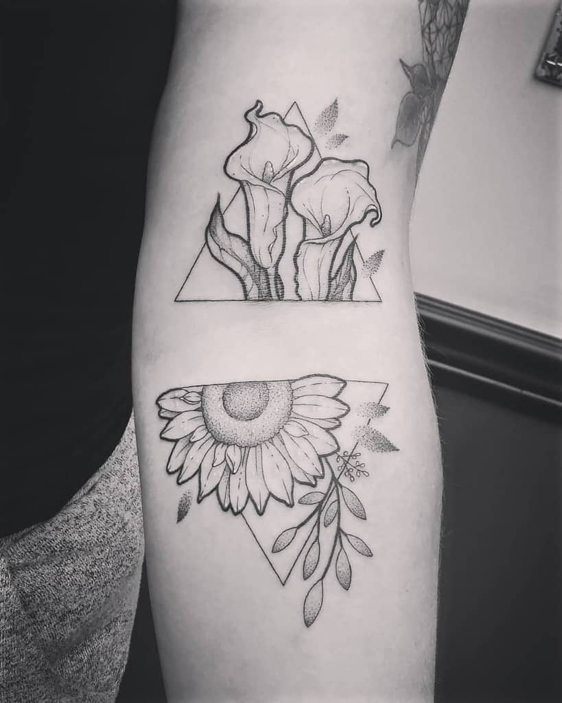medium-sized black and grey geometric tattoo of a sunflower and callalilies in two triangles on woman's arm