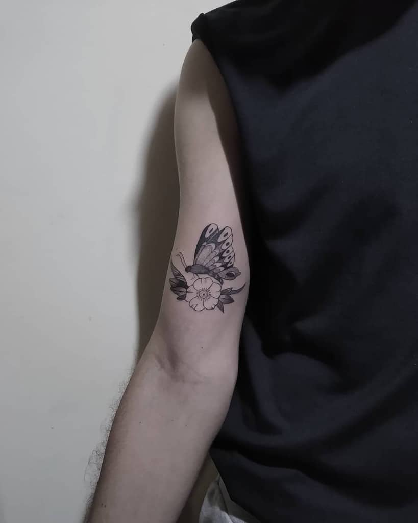 medium-sized black and grey tattoo on man's upper arm of realistic butterfly on a hibiscus flower